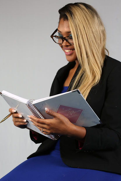 Woman is holding an open business planner while smiling.