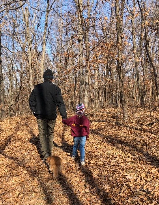 The author walking in the woods, holding the hand of his young grand-neice