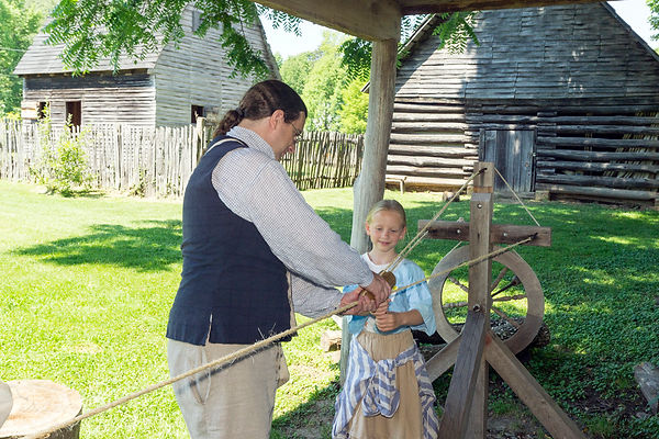 Man in colonial clothes showing girl the ropewalk