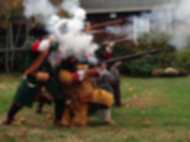 Group in colonial clothes firing muskets