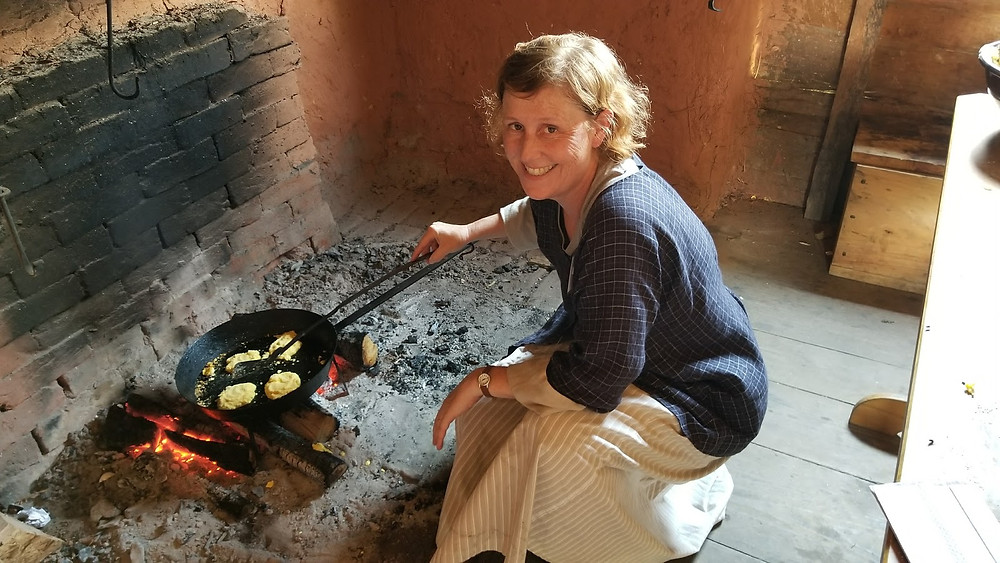Woman in colonial clothing cooking over the hearth in the Lord Mayor's Tenement