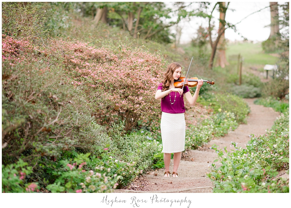 Girl playing violin in gardens