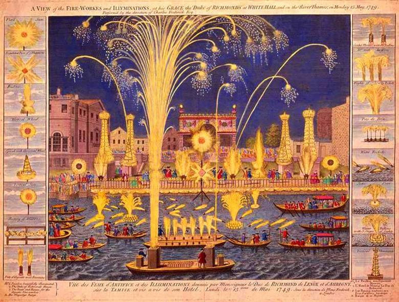 Nighttime city scene with buildings and the background and boats on the river in the front. Everything is lit up with fireworks.
