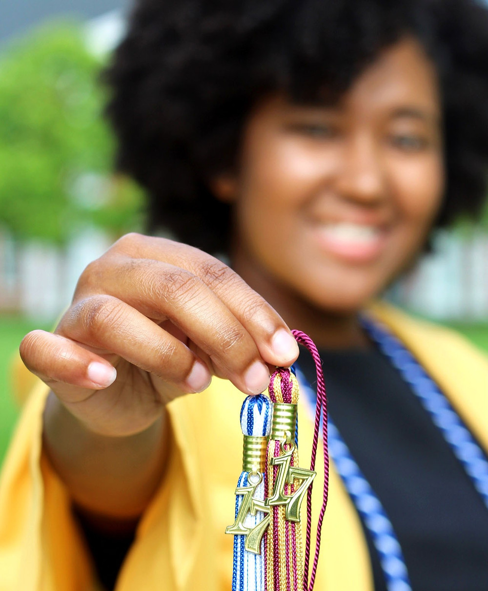 Amara Leggett (A Young Legend) is holding two of her graduation cap tassles with the year 2017 on it to signify that she graduated high school and college simultaneously.