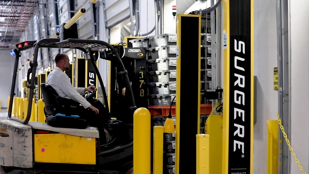 Forklift carrying returnable containers through Surgere portals.