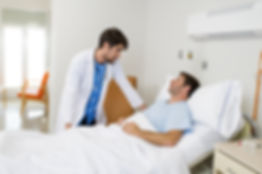 doctor consulting patient lying on hospi