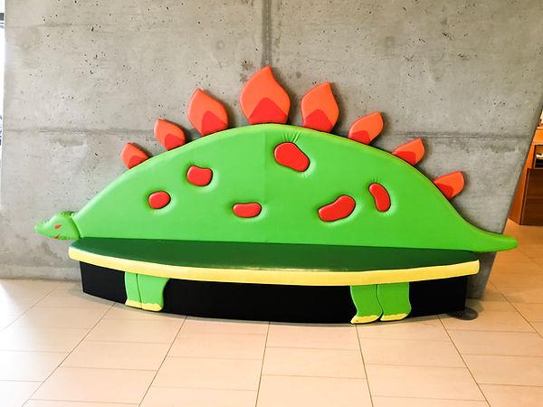 A dinosaur shaped bench