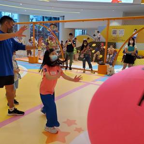 港隊運動員協助小朋友推起健球,做開波的姿勢。