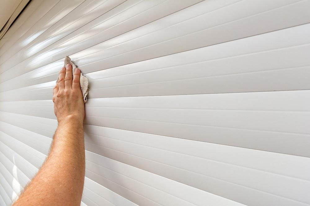 Preventative Measures For Garage Door Owners - Hand and cloth wiping garage door