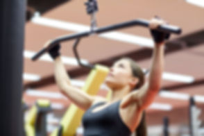 woman flexing arm muscles on cable machine in gym.jpg