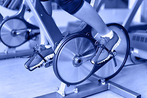 Exercise bike with spinning wheels. Woman excising biking in fitness center. closeup of pedals. Prof