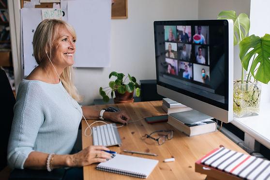 Smiling mature woman having video call v