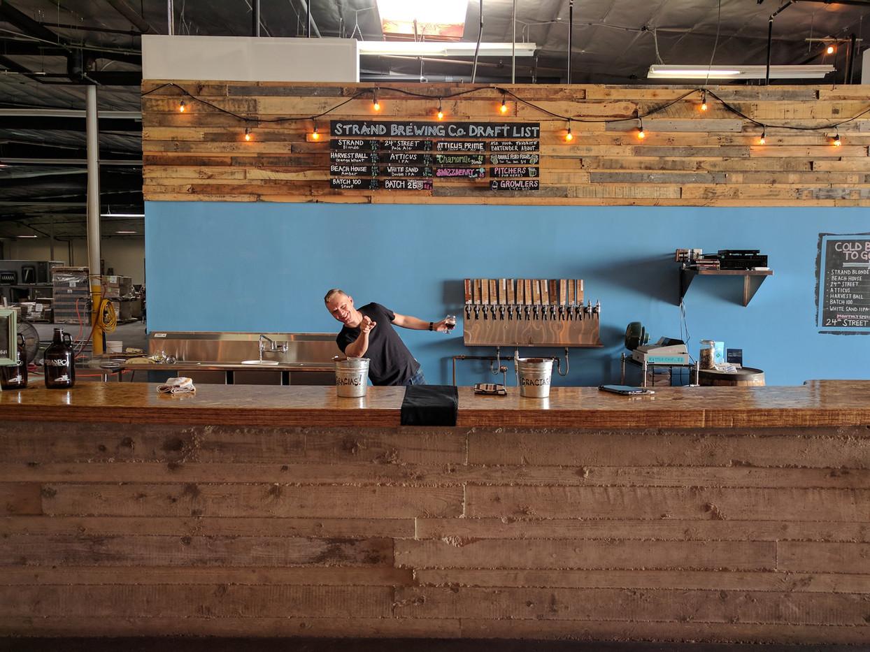 32 Strand Jonas behind bar pointing.jpg