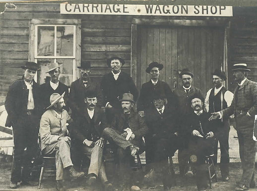 GROUP OF MEN POSED OUTSIDE CARRIAGE & WAGON SHOP