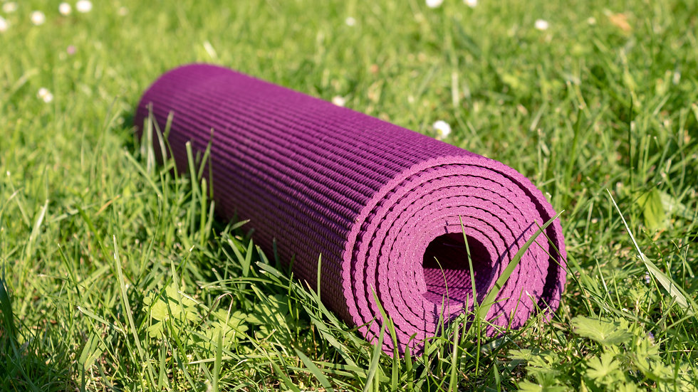 Rolled Yoga mat on green grass with sunl