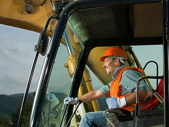 male operator driving excavator on const