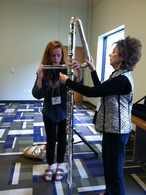 Longtime member Penny Griffey letting festival attendees play her contrabass flute, 2014