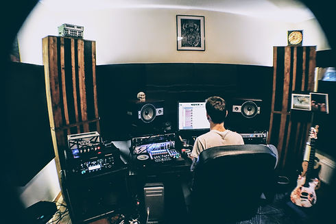 André Six's studio. He's seen from the back, working on a session, there are guitar amps and audio gear all around him.