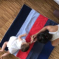Mama und Kind spielen auf bunte batina Baumwolle Krabbeldecke