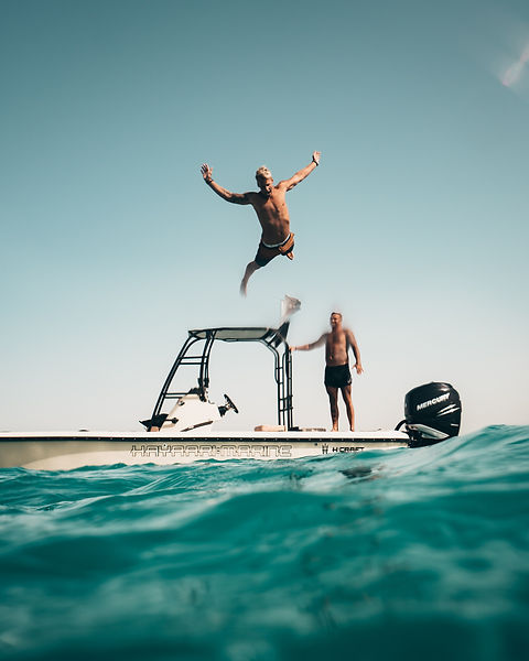 photo-of-man-jumping-from-boat-to-the-se