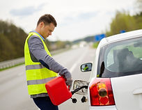 Man refuelling her car on a highway road