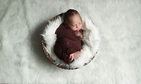 Newborn boy swaddled in wrap in a bowl on white flokati by Bmariephotography