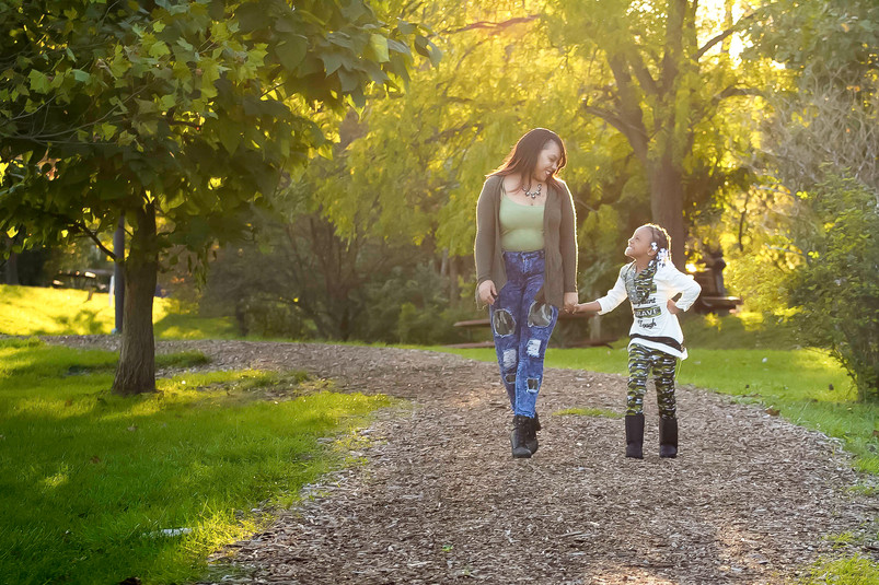Mom and daughter walking in forest during fall laughing portrait by bmariephotography