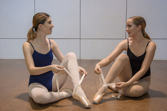 Dancers puuting on pointe shoes