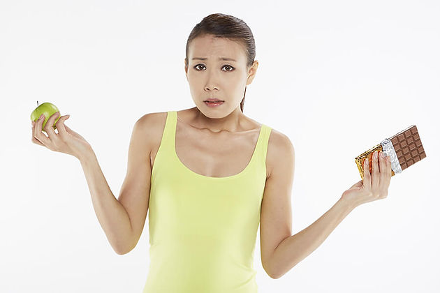 A photo of a woman with an apple in one and and chocolate in the other.