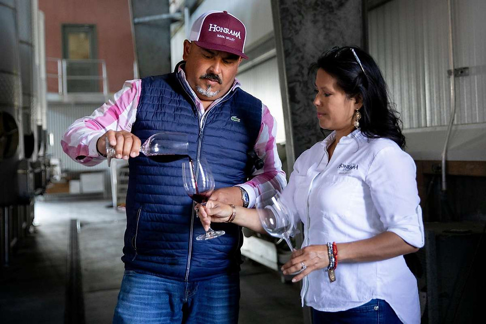 Juan Puentes pours a taste of Pinot Noir straight from the tank for his wife Miriam at the Honrama Cellars tasting room.  | Jessica Christian / The Chronicle