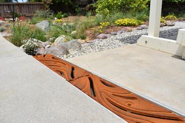 Iron Drain with Swirls in Landscape