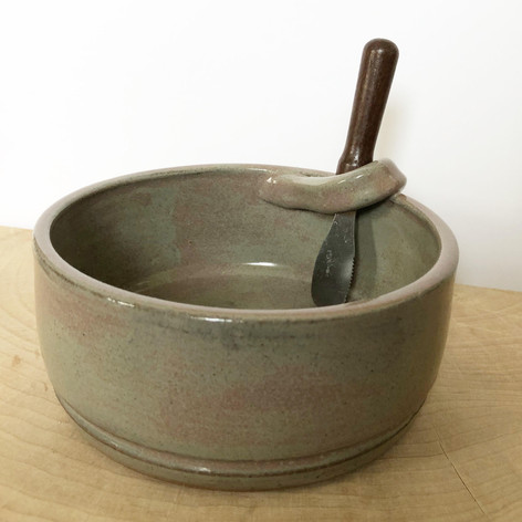 Brown ceramic dip bowl with small spatula
