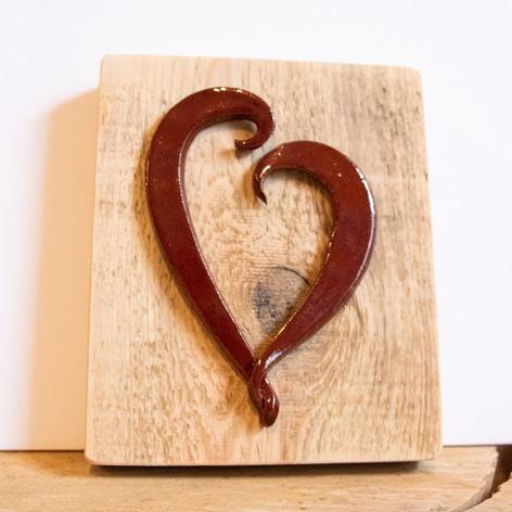 Red ceramic heart on barnwood