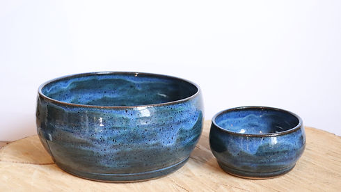 Small and large ceramic blue bowl on woo