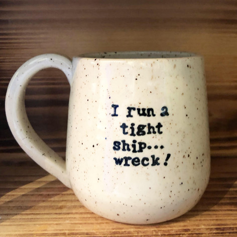 Speckled white ceramic mug with text