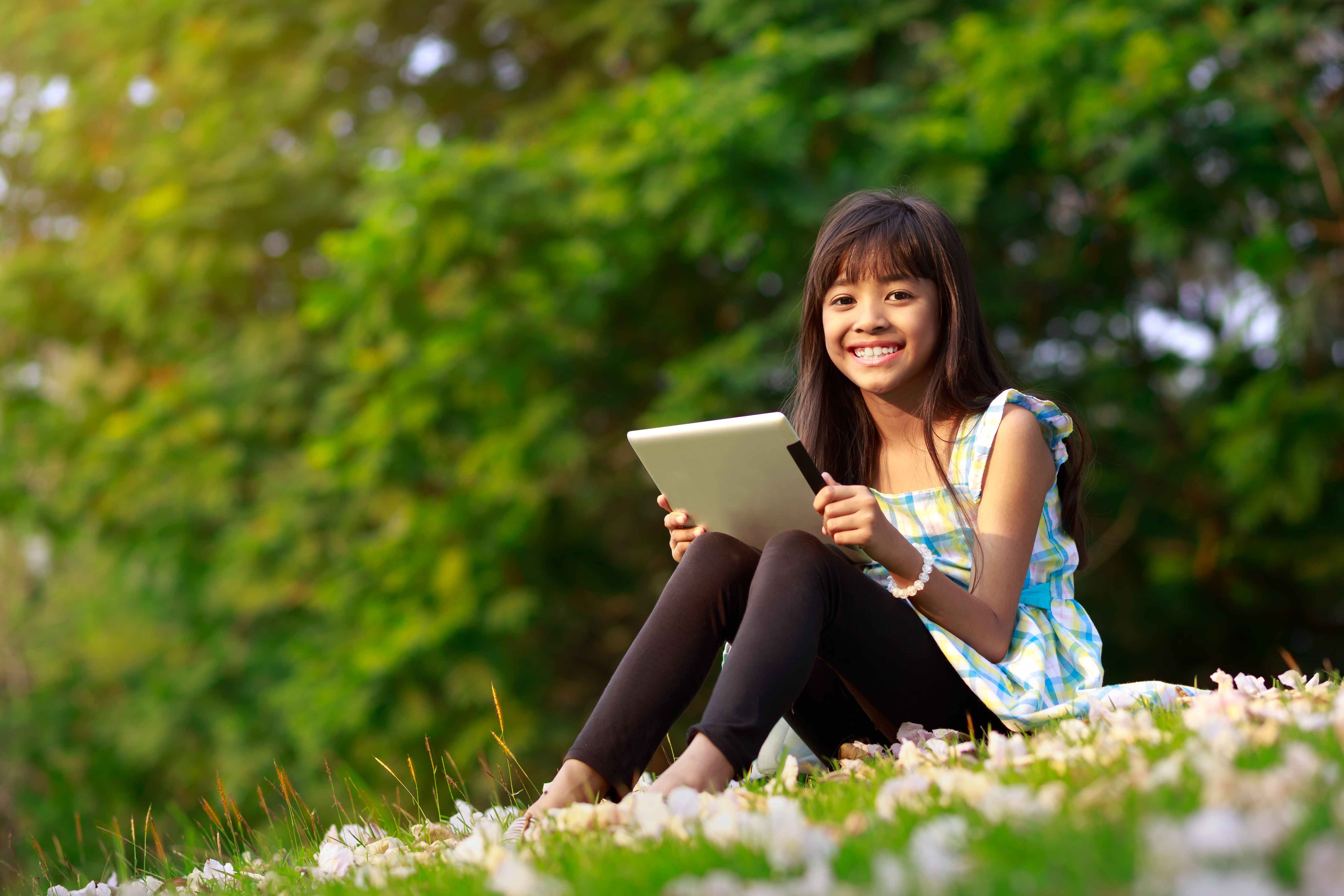 Happy asian girl sitting on grass with t