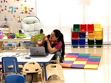Academia Elze Child Care Center. Teacher reading a book.