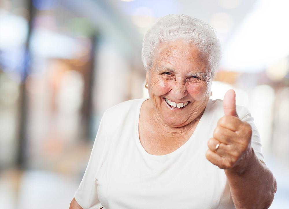 Señora mayor sonriendo con dentadura ajustada