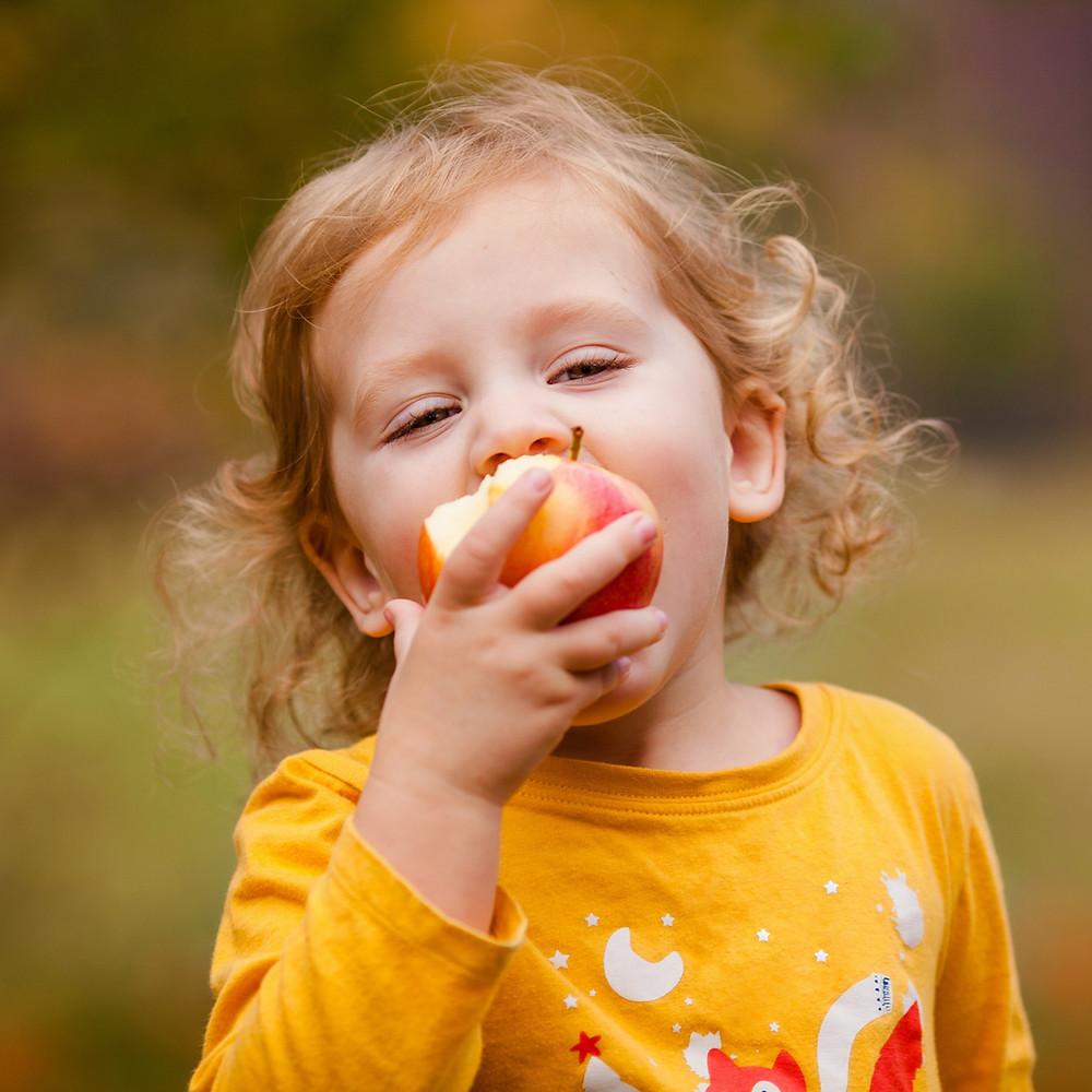 Niña masticando una manzana