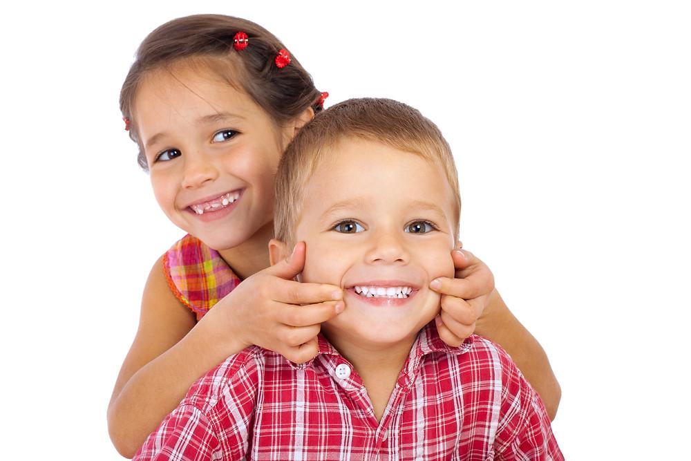 Niños sonriendo sin manhas en los dientes