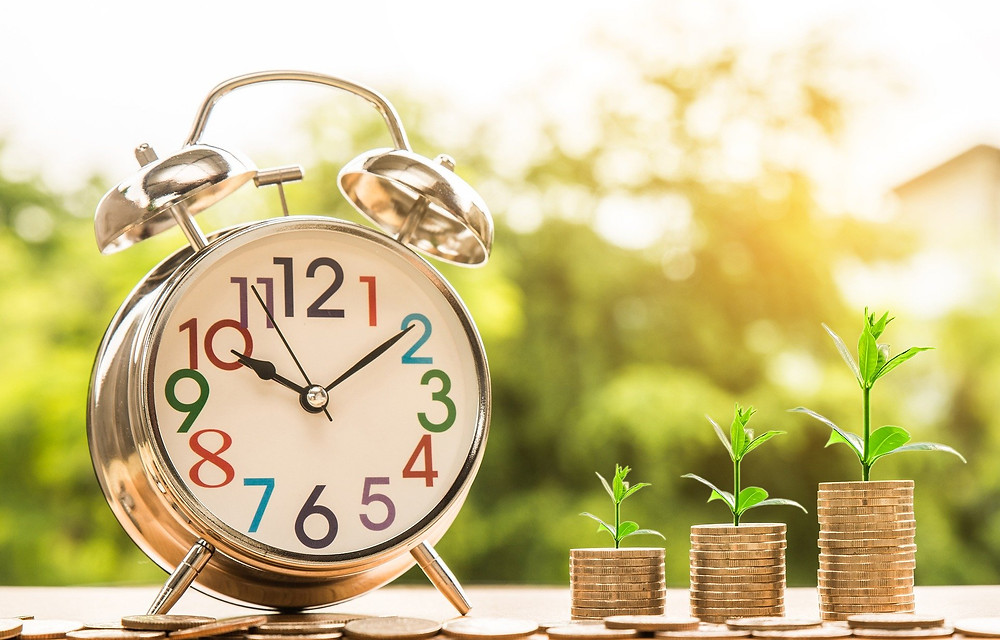 Stacks of coins with plants growing on them, placed next to a clock, representing how looking at freight as a Cost-Plus-Logistics model can bring you steady profit over time.