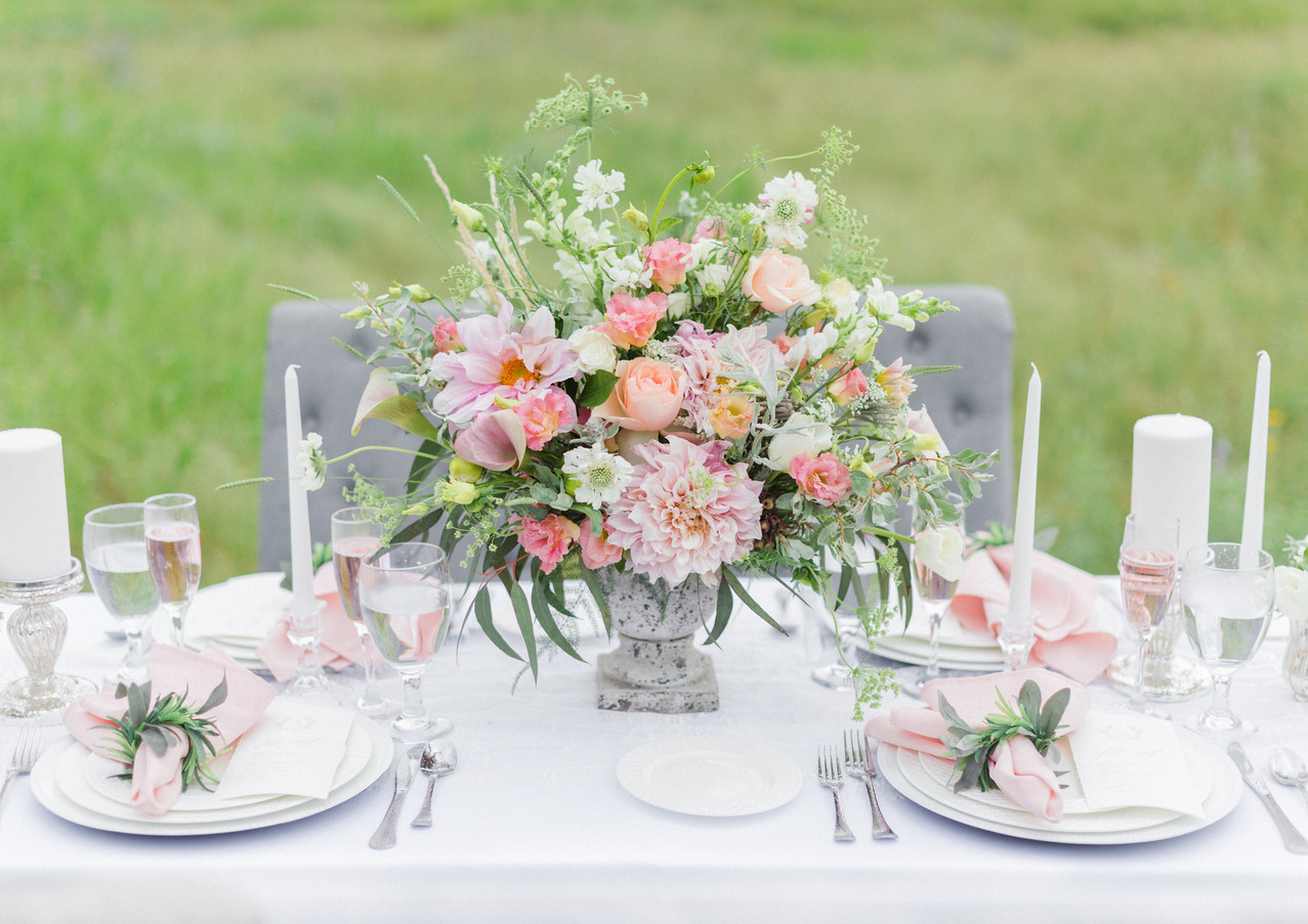 Runner: White Lace Centerpiece: Designed with Stone Vase, Mercury Vases, Glass Candleholders, and Mercury Pillars Chargers: White Napkins: Blush with Greenery Napkin Ring  Floral: Soul and Stem Photo: Paige Marie Photography Background: Blue Mountain