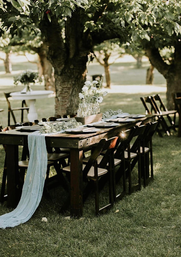 Runner: Greenery Garland (Client also used Dusty Blue Cheesecloth) Centerpiece: Pre-Designed Style 15 Charger: White Napkin: Dark Grey  Photo: Elsa Eileen Photography Venue: Flathead Backyard Orchard