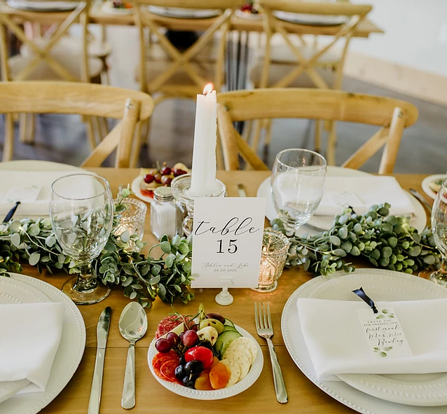Runner: Eucalyptus Garland with Twinkle Lights Centerpiece: Designed with Glass Candleholders and Vintage Votives Chargers: White Napkins: White  Photo: Honeybee Photography Venue: White Raven