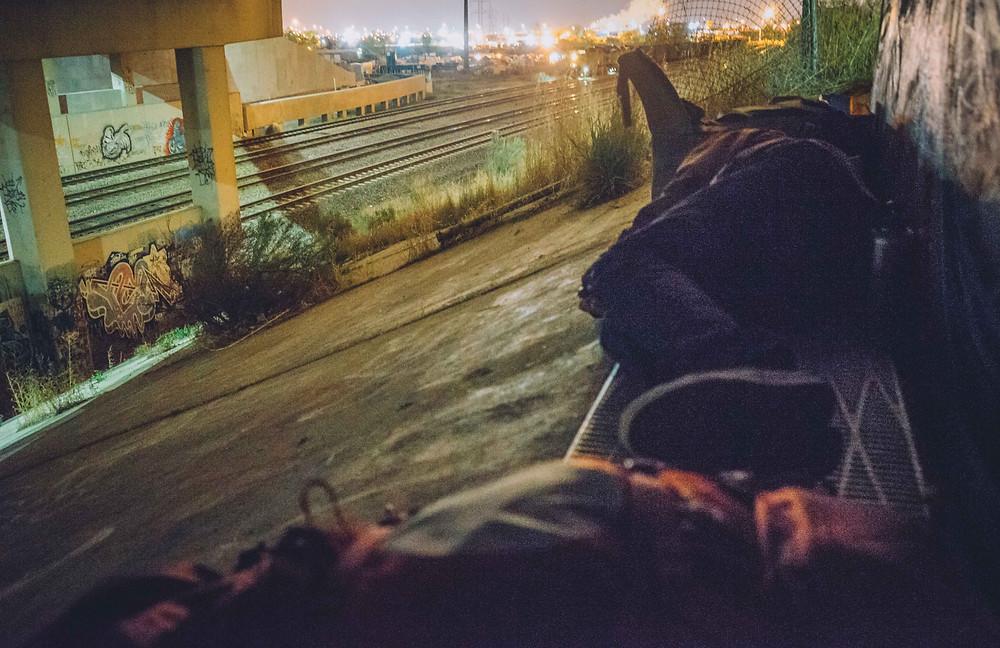 Guy sleeping under train bridge, waiting to catch train