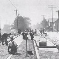 Installing wood pavers on a main street between train tracks. c.1910