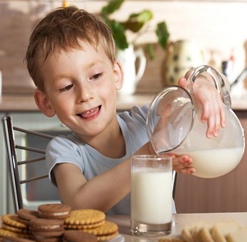 Milk boy glass of fresh milk, table biscuits