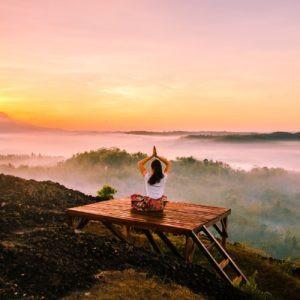 Femme faisant du yoga devant un paysage majestueux.