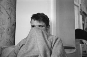 Homme se cachant le visage avec son chandail. On ne le voit qu'à partir des yeux.
