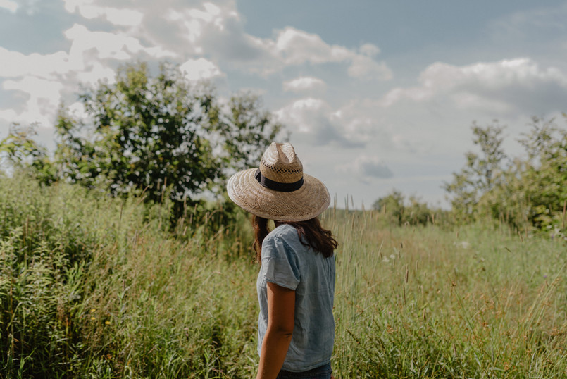 woman in hat at anthill farm agroforestry